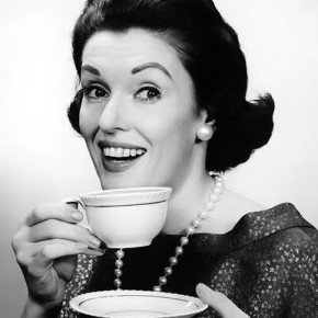 Vintage photo of woman with teacup, smiling.